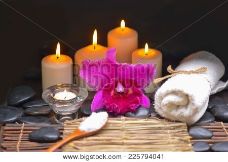 Spa setting with red orchid, set of candle, black stones,salt in spoon,oil on mat