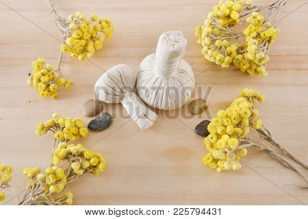 spa setting with yellow helichrysum flowers, herbal ball.stones, on wooden background