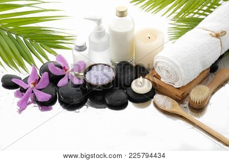 Spa still life with black stones and orchid, candle, salt in bowl ,roller on bowl, bottle, oil,palm