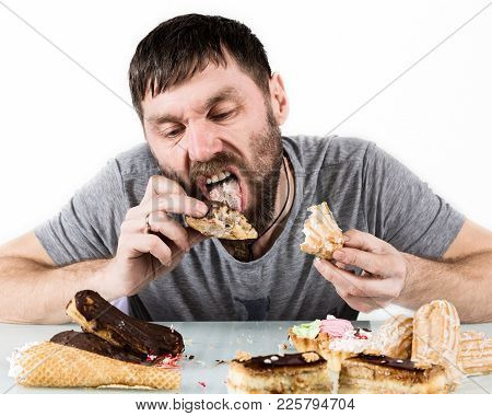 Glutton Bearded Man Eating Cupcakes With Frenzy After Long Diet. Harmful But Delicious Food.