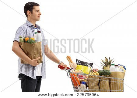 Young man with a shopping bag and a shopping cart filled with groceries isolated on white background