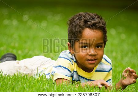 Cute Little Hispanic Boy Smiling And Outside Playing.