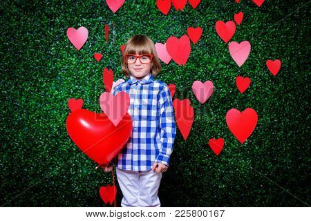Ð¡ute child boy holding heart shaped balloon, surrounded by little hearts over lawny background. First love. Valentine's Day.