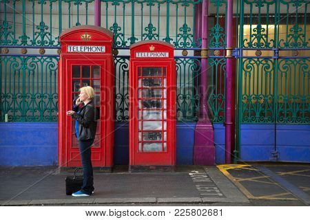 LONDON-ENGLAND, June 10, 2017:  Blond woman talking on mobile phone in front of 2 red phone booths model K-2 made in Smithfield market the largest wholesale meat market in the UK