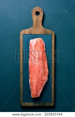 high angle view of a frozen fillet of salmon on a slate and wooden tray, placed on a dark green surface