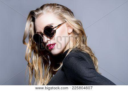 Attractive blonde young woman wearing black sunglasses. Studio shot. Beauty, fashion concept. Optics style.