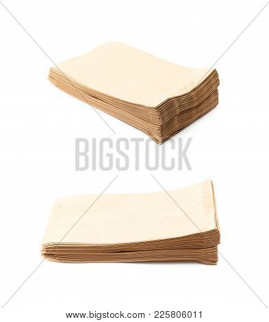 Pile Of Folded Paper Bags Isolated Over The White Background , Set Of Several Different Foreshorteni
