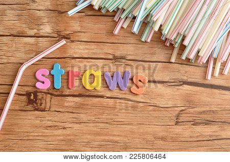 Colorful Straws With The Word Straws On A Wooden Background