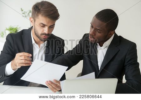 Diverse Business Partners In Suits Holding Documents Discussing Reading Contract Terms, Serious Focu