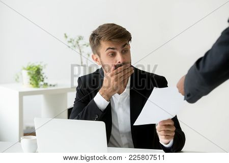 Surprised Confused Caucasian Employee Receiving Dismissal Notice, Letter Or Document With Unexpected