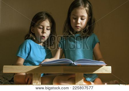 A Girl Reads A Book For The Night Of Her Younger Sister