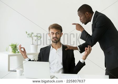 Caucasian Employee Meditating At Workplace Ignoring Angry African Boss Scolding Him, Calm White Offi
