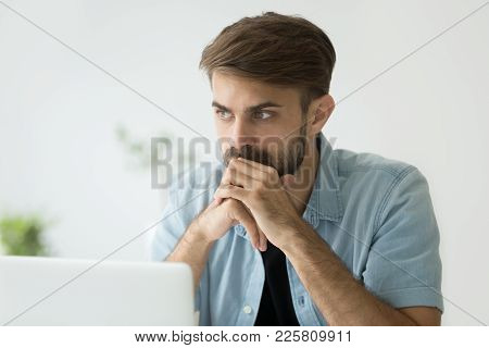 Thoughtful Serious Young Man Lost In Thoughts In Front Of Laptop, Focused Businessman Or Absent-mind