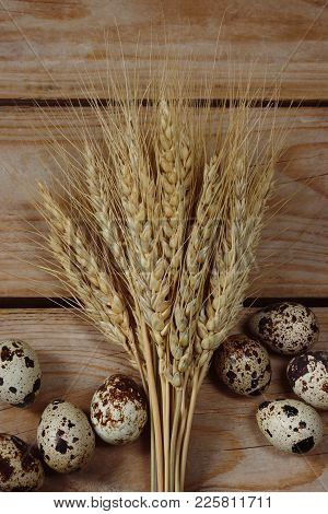 Easter Eggs With Wheat Spikelets On The Boards.