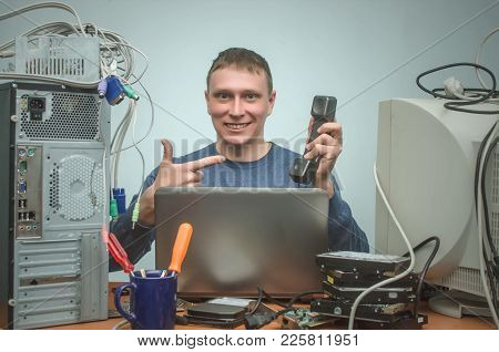 Happy Cheerful Computer Technician Engineer Of User Support Service Is Sitting In Front Of Laptop An