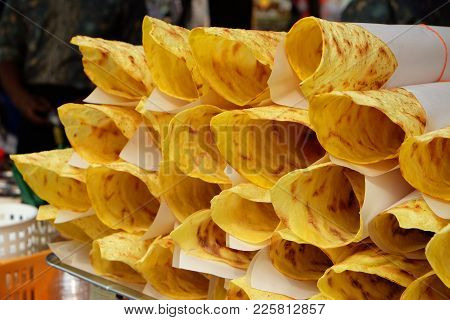 Crispy Thin Fried Roti With Sweetened Condensed Milk On Top, Rolled Inside Paper, Ready To Serve For