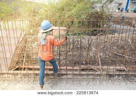 Construction Worker Assembling Rebar Steel At Construction Site.