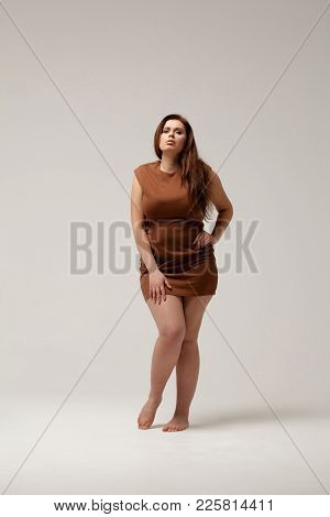 Nice Overweight Female Posing In Brown Short Dress. Diet Concept.