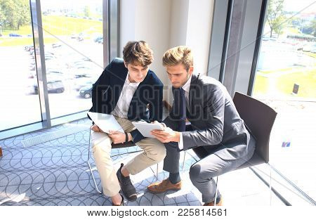 Mature Businessman Using A Digital Tablet To Discuss Information With A Younger Colleague In A Moder