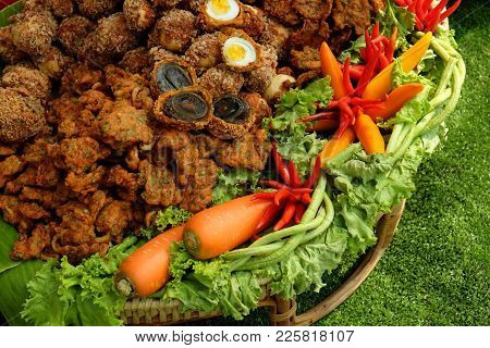Hard Boiled Chicken Eggs And Century Eggs Covered By Fried Fish Patty On The Rattan Tray Decorated B