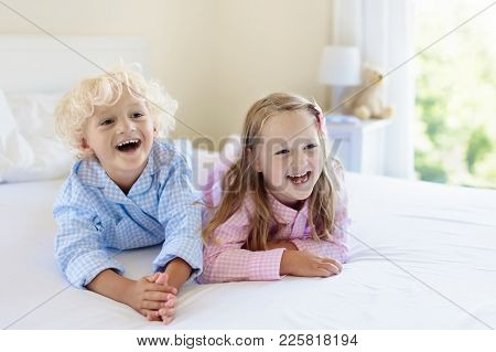 Kids Playing In Parents Bed. Children Wake Up In Sunny White Bedroom. Boy And Girl Play In Matching