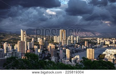 Benidorm Skyscrapers At Dusk With Sun Light And Stormy Clouds