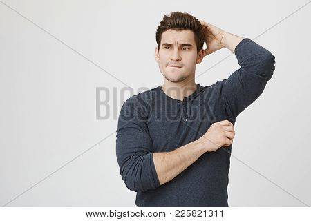 Indoor Shot Of Thoughtful Attractive Man With Trendy Haircut And Stubble, Looks At Camera With Pensi