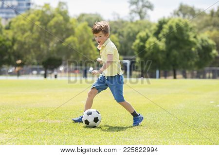 Young Little Kid 7 Or 8 Years Old Enjoying Happy Playing Football Soccer At Grass City Park Field Ru