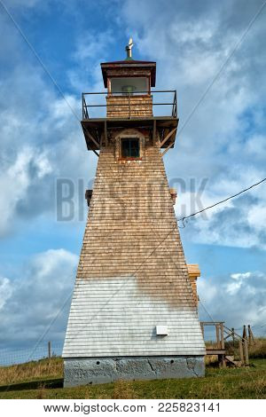 Old Cape Tryon lighthouse with a nice blue sky with clouds in Prince Edward island in Canada
