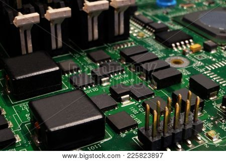 Closeup Of Green Electronic Circuit Board With Many Chips And Ics