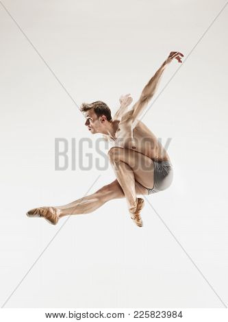 The Male Athletic Ballet Dancer Performing Dance Isolated On White Background. Studio Shot. Ballet C