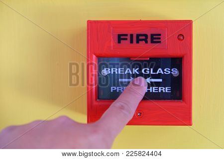 Fire Alarm Box Switch With Finger About To Press The Glass For Triggering Alarm On