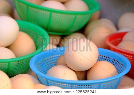 A Raw Fresh Egg In The Multicolored Basket Selling At The Market