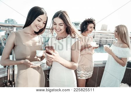 Pleasant Interaction. Cheerful Nice Positive Women Standing Together And Talking To Each Other While