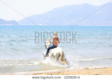 Young female riding her horse in the sea in Greece poster