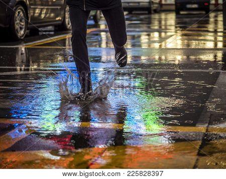 Crop Shot Of Man Splashing Water In Puddle On Pavement Reflecting Night City Lights.