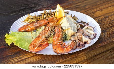 The Street Food, Seafood Served On The Paper Plate. The Green Letuce, Kalamari, Shrimps.