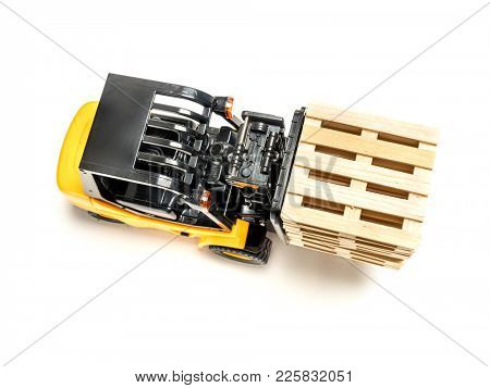 Forklift truck carrying stacked wooden pallets shot from above on white background