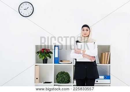 Portrait Of Businesswoman In Hijab With Folder In Hands In Office