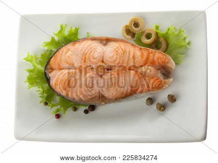 Baked Steak Of Salmon With Olives, Capers And Lettuce On The Plate