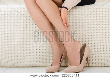 Partial View Of Woman Having Discomfort While Sitting On Sofa