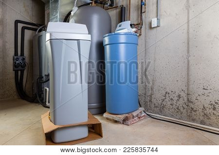 Old And New Water Softener Tanks In A Utility Room Waiting For Replacement To Remove Minerals From H