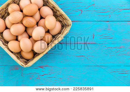 Rustic Wicker Basket Filled With Healthy Farm Fresh Free Range Brown Eggs Viewed From The Top Over A