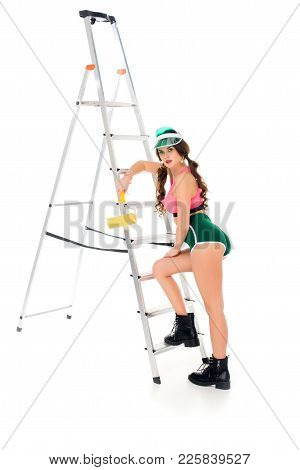 Beautiful Girl In Visor Holding Painting Roller Near Ladder, Isolated On White