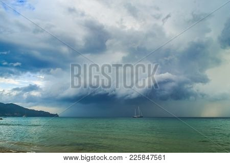 White Yacht Sailing In Stormy Sea. Dark Thundery Night Background. Dramatic Storm Cloudscape. Danger