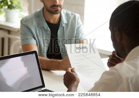 African American Hr Manager Holding Applicants Curriculum Vitae At Job Interview, Black Recruiter Or