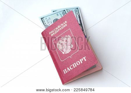 Two Banknotes Of 100 American Dollars Each, Lying In The Russian Passport On A White Background.