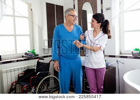Young Beautiful Nurse Helps To Senior Man