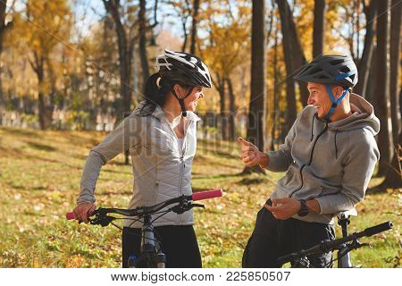 Happy Young Couple Having Fun Riding A Bicycle On Sunny Autumn Day In The Park. Two People Are Talki