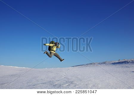 Man Is Jumping On The Winter Sky. It Is Cold And Snowy. The Man Is Active And Enthusiastic. Winter O